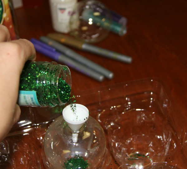 Holiday Crafts for Kids Homemade Glitter Ornaments- adding glitter